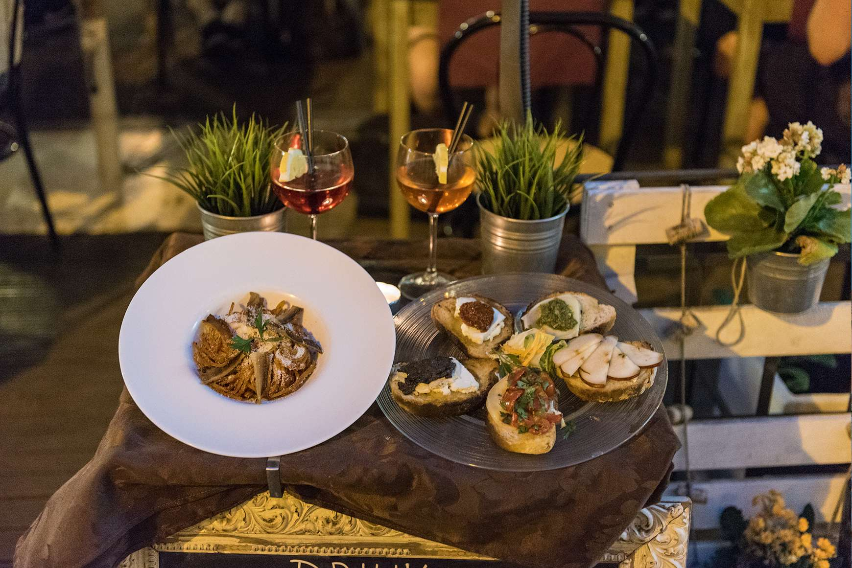 Italian bruschetta and pasta dish served on outdoor table