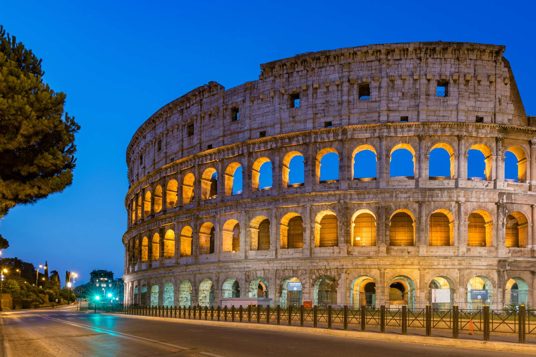 Partial view of arched facade of Colosseum at dusk
