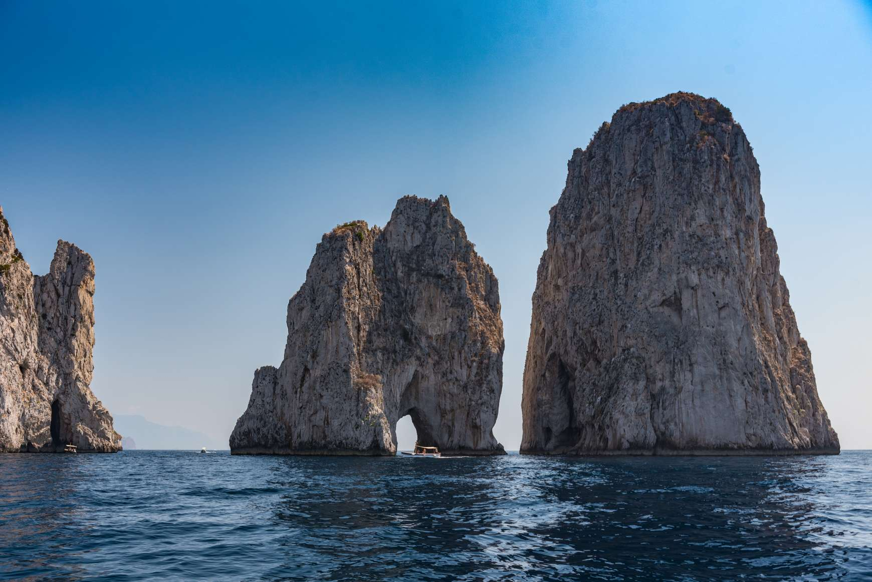 The three Faraglioni rocks of Capri jutting out from the sea