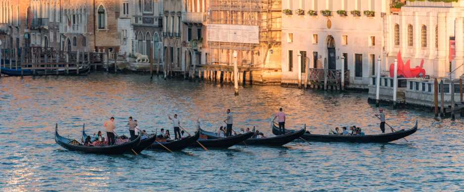 Row of passenger-filled gondolas crossing the Grand Canal at sunset