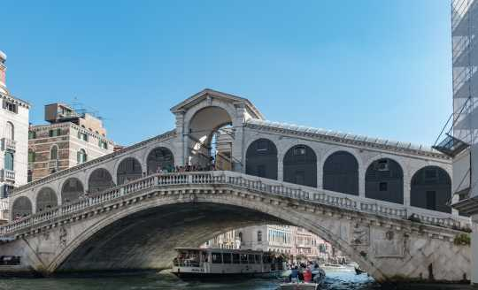 Side view looking up at the Rialto Bridge in Venice Italy