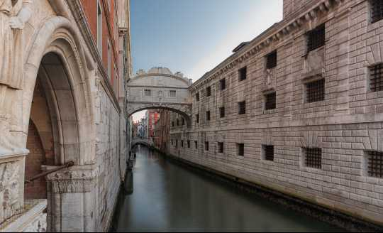 Looking up at the Bridge of Sighs from a canal in Venice, Italy