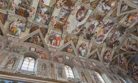 Looking up at the side panels of the Sistine Chapel inside the Vatican