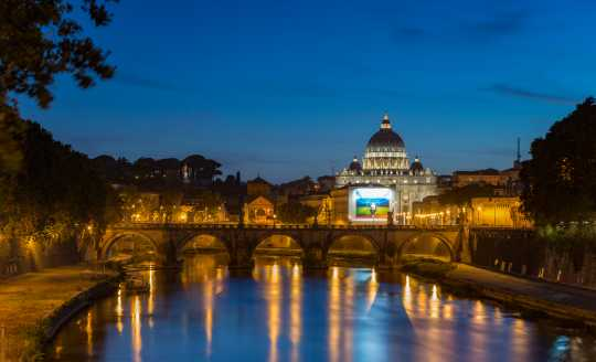 Illuminated evening view of St. Peter's Basilica in Rome