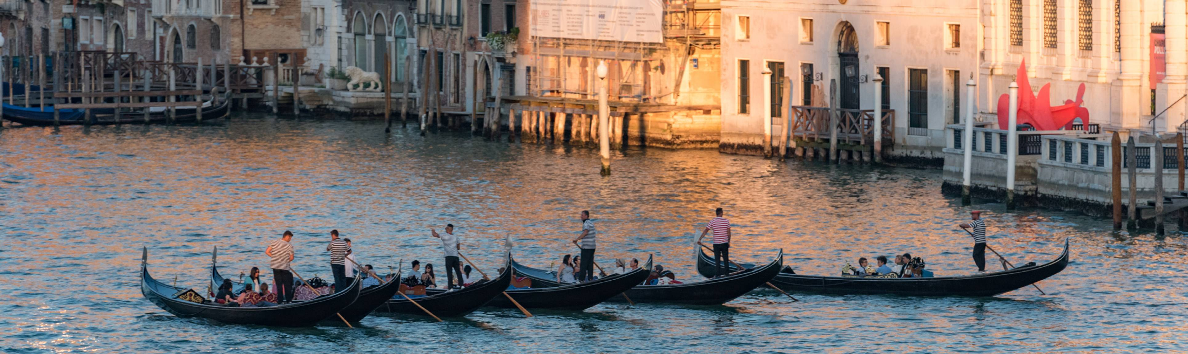 Sunset view of passenger-filled gondolas crossing the Grand Canal