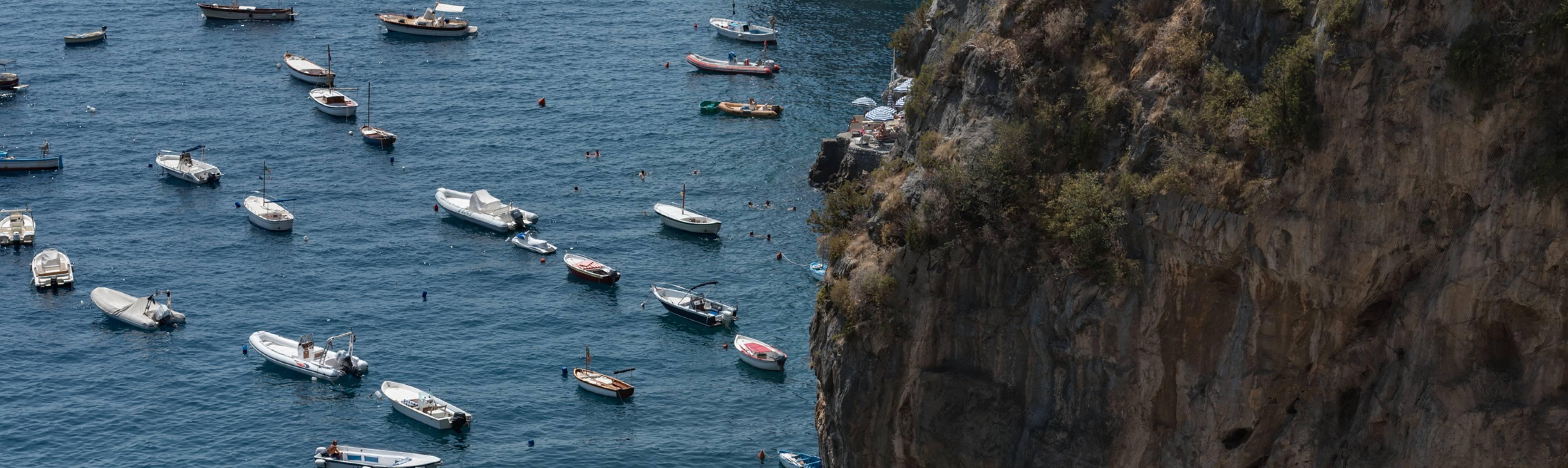Cliff view looking down at ships at sea of the Amalfi Coast