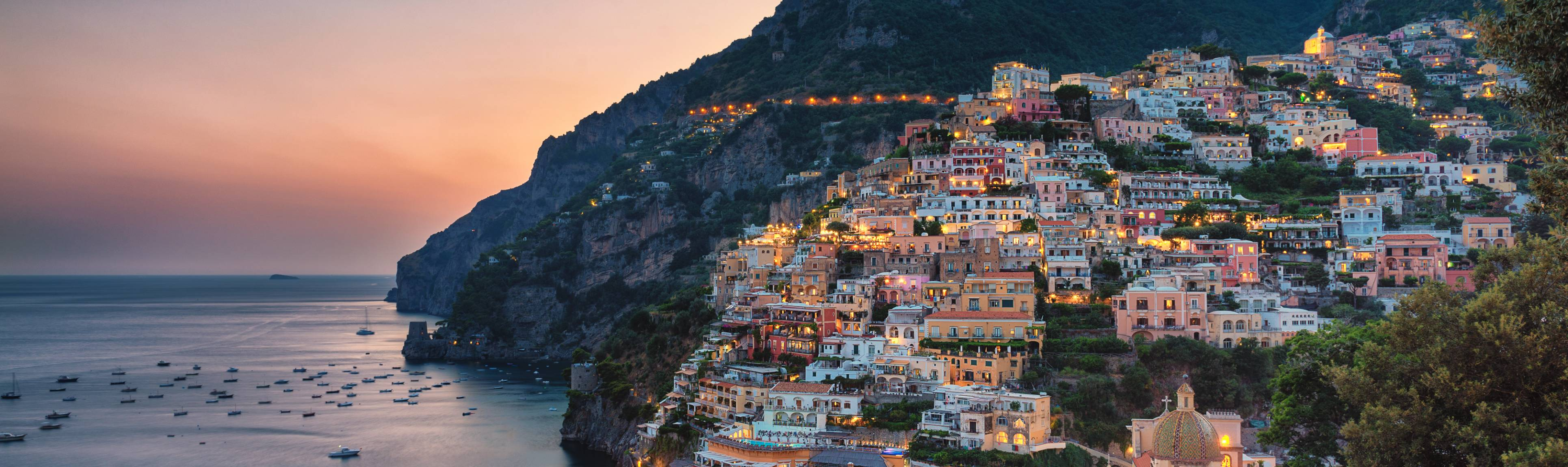 View of Positano nestled against the mountains at sunset, Amalfi Coast