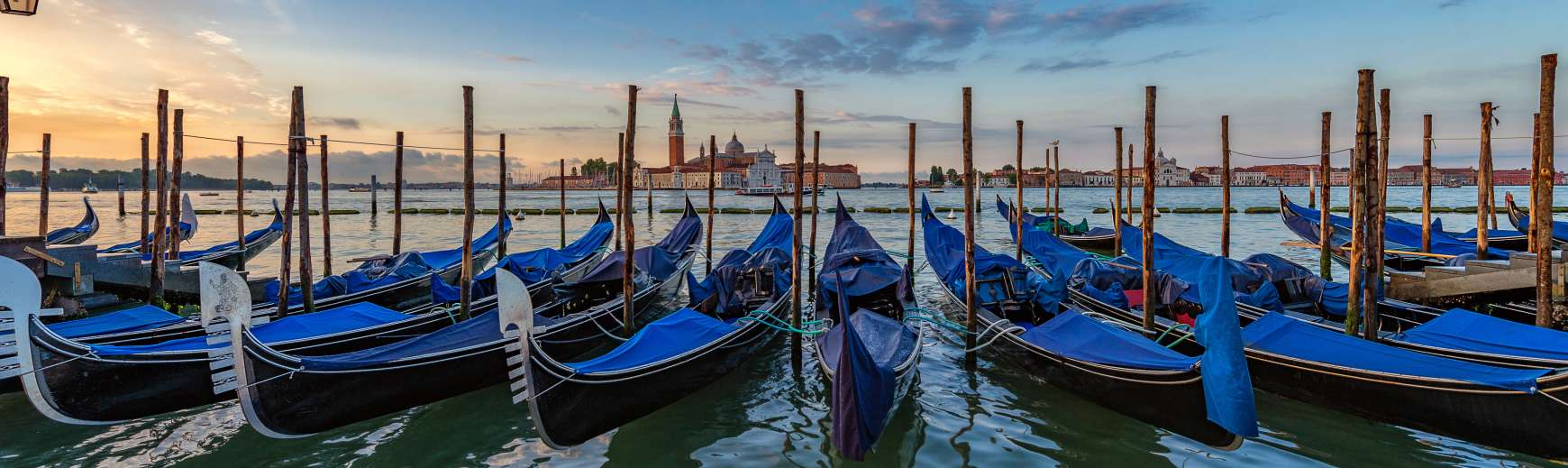 Row of gondolas covered by blue tarps, Venice Italy Vacation Packages
