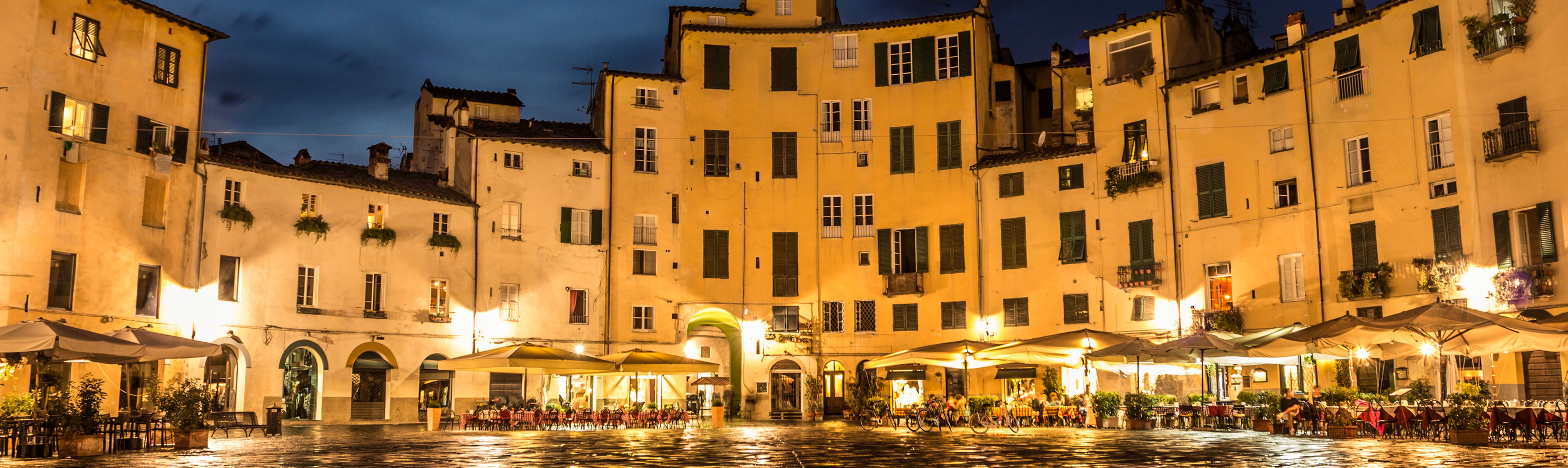 Evening lights illuminate the Piazza Dell'Anfiteatro in Lucca, Italy