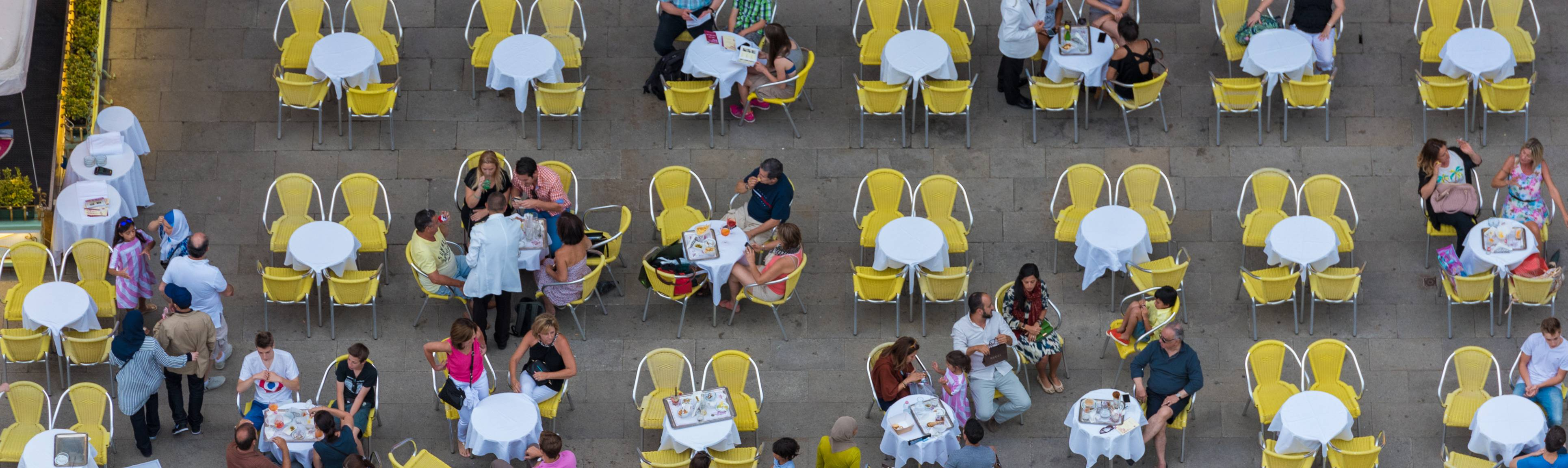 Bird's eye view of people sitting at small tables in a Piazza