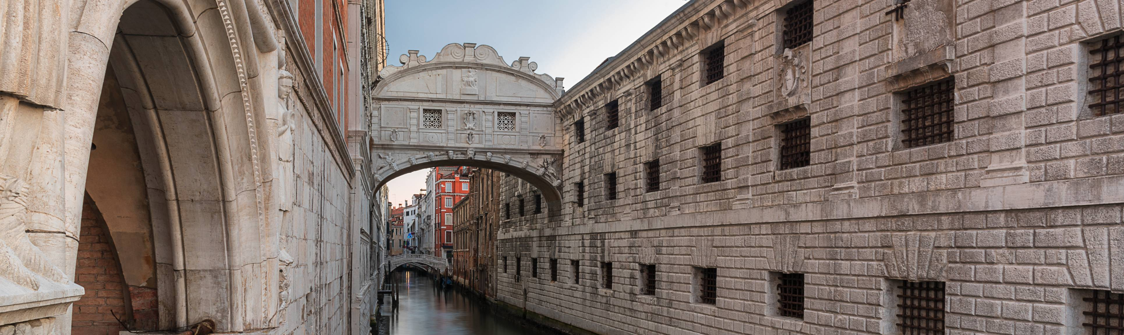 The Bridge of Sighs hangs from third story above Venice's canal.