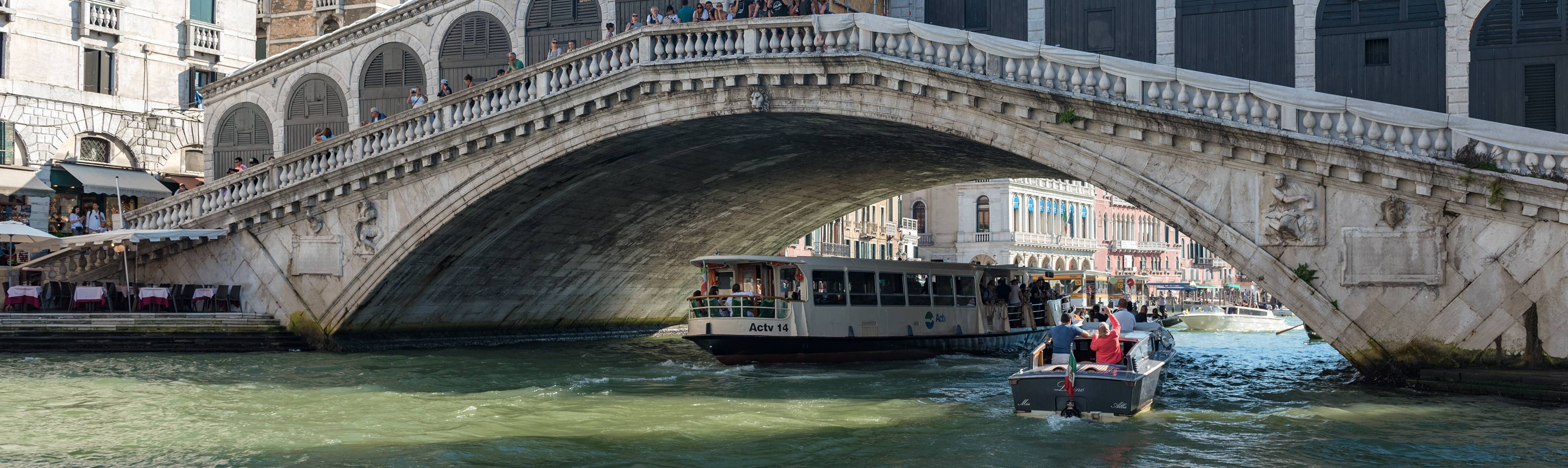 Water taxi crossing under the Rialto Bridge in Venice, Italy