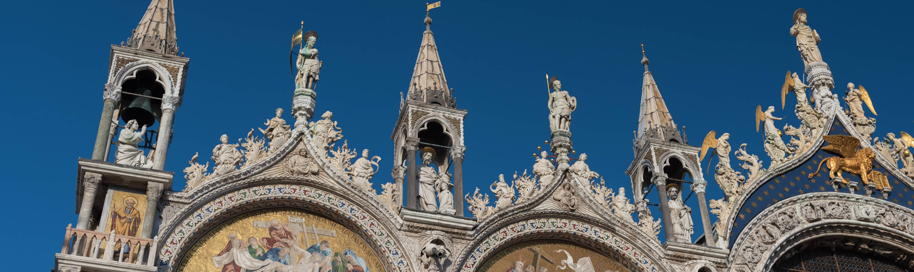 Fascia of St. Mark's Basilica adorned with statues & spires in Venice