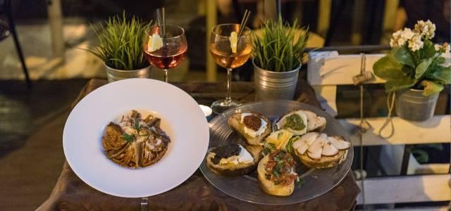 Italian bruschetta and pasta dish served on outdoor table