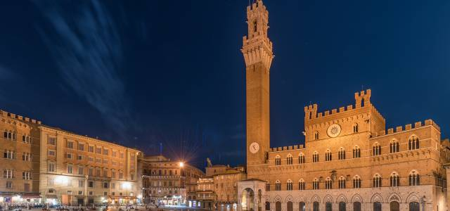 Evening view of tower and buildings at Palazzo Pubblico in Siena, Italy