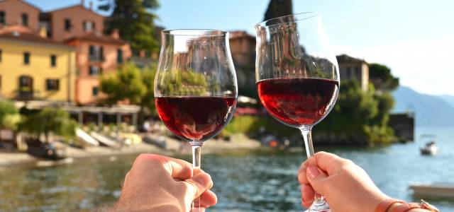 Two glass of red wine toasting with Lake Como in the background