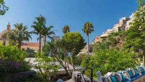 View of Amalfi through courtyard of palm trees
