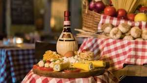 Detail of table with cheese, fruits and wine in Italy