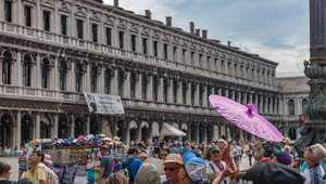 Piazza San Marco filled with visitors, flanked by arches of loggia