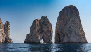 View of Faraglioni cliffs jutting out of the sea at Capri Island in Italy